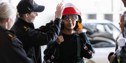 One of the Defence Work Experience Program participants, Jada Brown, tries on firefighting equipment with the help of Able Seaman Aviation Support Emma Stewart during a tour of HMAS Albatross.