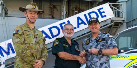Commanding Officer HMAS Adelaide Captain Jonathan Ley, with Colonel Kim Gilfillan, presents the keys to the new ambulance to Sir Douglas Kelson. Photo: Leading Seaman Kieren Whiteley