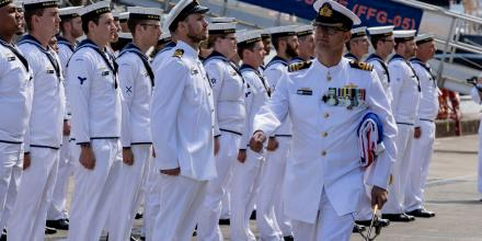 HMAS Melbourne's final Commanding Officer, Commander Marcus Buttler, carries the ship's Australian White Ensign away during the decommissioning ceremony. Photo: PTE Rodrigo Villablanca