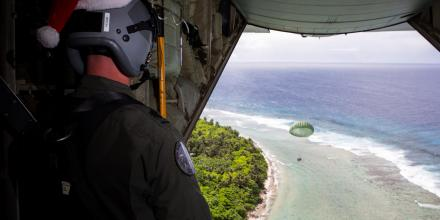 Number 37 Squadron C-130J Hercules loadmaster Warrant Officer Nicholas Stubbs-Race watches as a box of donations floats down to the Micronesian island of Magur during Operation Christmas Drop. Photo: Corporal David Said
