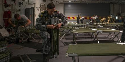 Petty Officer Marine Technician Brendan McDermott assembles stretcher beds on HMAS Adelaide. Photo: Able Seaman Thomas Sawtell