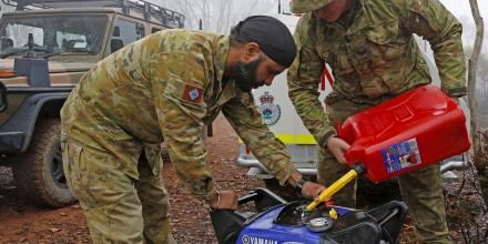 Private Manpreet Singh and Corporal Luke Ford, of the Brisbane-based 7th Combat Services Support Battalion, refuel a generator which powers a RFS re-transmitter. Photo: Sergeant Dave Morley