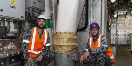 Petty Officer Nathan Austin, left, and Lieutenant Ryan Webb inspect one of the ventilation fans on board HMAS Adelaide at Garden Island, Sydney. Photo: Able Seaman Sittichai Sakonpoonpol