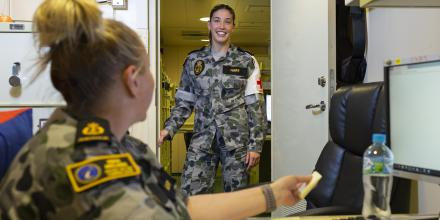 Able Seaman Stephanie Hart speaks with one of her ship mates on board HMAS Adelaide. Photo: Able Seaman Jarrod Mulvihill