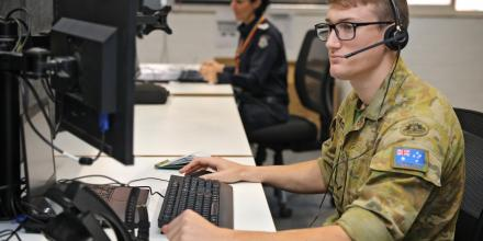Lance Corporal William Paffrath working at the Police Assistance Line takes phone calls from members of the public. Photo: Petty Officer Nina Fogliani