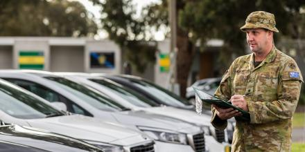 Logistics officer Major Adrian Sneddon checks off vehicles used for Operation COVID-19 Assist at Simpson Barracks, Victoria. Photo: Leading Aircraftman John Solomon