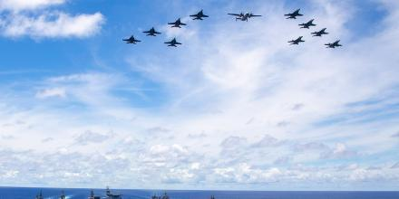 Ships from the RAN, US Navy and Japan Maritime Self-Defense Force sail in company through the Philippine Sea as aircraft from US Carrier Airwing 5 fly above. Photo: Leading Seaman Ernesto Sanchez