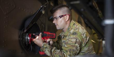 Craftsman Charles Dodds conducts maintenance on an Army Tiger armed reconnaissance helicopter on board HMAS Canberra. Photo: Petty Officer Tom Gibson