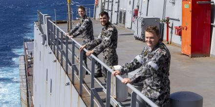 Midshipman Mitchell Sutton, left, Able Seaman Ethan Macnamara and Able Seaman Ben Ashman on the bridge wing of HMAS Choules as the ship returns from Vanuatu. Photo: Leading Seaman James McDougall