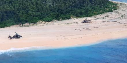 An Australian Army ARH Tiger helicopter lands on Pikelot Island in Micronesia. The SOS message of the stricken sailors can be seen on the beach.