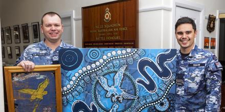 Wing Commander Trent Harris, left, and Flight Lieutenant Tjapukai Shaw display the new Aboriginal artwork commissioned for No. 22 Squadron Headquarters. Photo: Corporal Dan Pinhorn