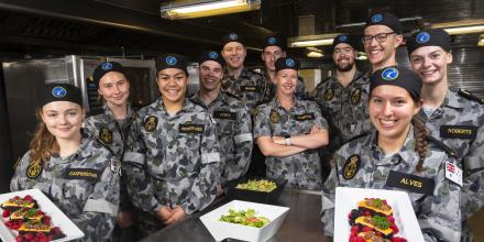 Petty Officer Maritime Logistics Chef Natalie Robinson, centre, with the gap year sailors and officers in the galley on board HMAS Adelaide during Exercise Sea Wader. Photo: Able Seaman Daniel Goodman