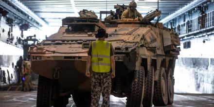 A soldier guides a Boxer Combat Reconnaissance Vehicle into position on HMAS Adelaide. Photo: Trooper Jonathan Goedhart