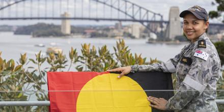 Able Seaman Boatswain's Mate Jahlaya Weazel with the Australian Aboriginal Flag at HMAS Kuttabul, Sydney. Photo:  Able Seaman Benjamin Ricketts