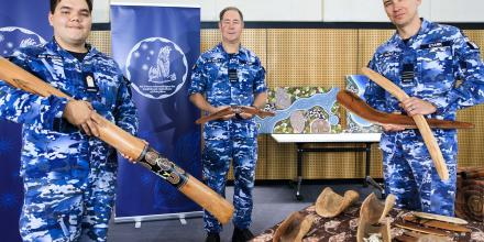 Air Force Officer Cadet Jaylin Lilley, left, explains the Indigenous artefacts on display at RAAF Base Williamtown to Group Captain Peter Cluff and Wing Commander John Stark. Photo: Corporal Brett Sherriff