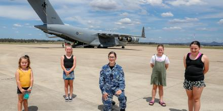 Leading Aircraftwoman Paige Madden, from No. 23 Squadron, with local Indigenous students Macy, left, Keira, Paige, Gabby and Addy on the flight line at RAAF Base Amberley. Photo: Corporal Nicci Freeman
