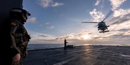 Lieutenant Commander Matthew Schroder, left, observes the departure of a US Navy MH-60R from HMAS Ballarat's flight deck during Exercise Malabar. Photo: Leading Seaman Shane Cameron