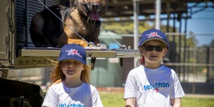 The 2020 Little Telethon Stars, Nora Holly and Eamon Doak, with military working dog Xeren during a visit to RAAF Base Pearce in Western Australia. Photo: Leading Seaman Richard Cordell