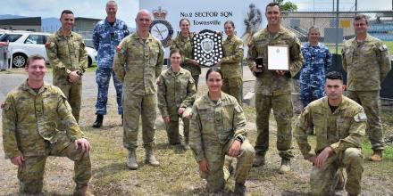 Officer Commanding No. 95 Wing Group Captain Mark Larter presents the Lady Hannah Shield to No.2 Security Forces Squadron in Townsville.