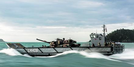 A light landing craft transports an Army M1A1 Abrams main battle tank during load trials with HMAS Canberra.