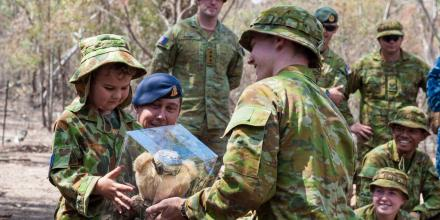 A trainee officer from ADFA's Foxtrot Squadron presents five-year-old James Roodt with an Army teddy bear.