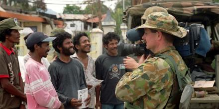 Sergeant Bill Guthrie films military information personnel as they spread the message of INTERFET's arrival in Suai. Photo: (then) Warrant Officer Al Green