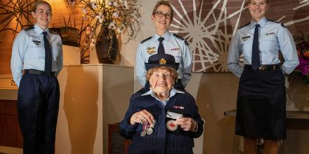 Leading Aircraftwoman Carley Dunn, left, Squadron Leader Del Gaudry, and Corporal Maddison Henry stand with Mrs Iris Terry during a formal presentation of a uniform at the Fairfield RSL. Photo: Corporal Kylie Gibson